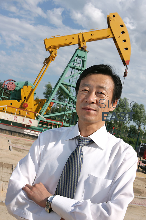 HEILONGJIANG PROVINCE, CHINA - July 13: Man standing by China National Petroleum Corp.'s 'nodding donkey' oil pumps on July 13, 2006 in Daqing, Heilongjiang province, China. China National Petroleum Corp is the mother company of PetroChina. (Photo by Lucas Schifres/Getty Images)