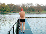 A member of the Serpentine Swimming Club walks along 'the Board' on a cold Winter's day, Hyde Park, London, UK. The Serpentine Lake is situated in Hyde Park, London's largest central open space. The Serpentine Swimming Club was formed in 1864 'to promote the healthful habit of bathing in open water throughout the year'.  Its headquarters were beneath an old elm tree on the south side of the lake, a wooden bench for clothing being the only facility.  At this time London was undergoing rapid expansion and Hyde Park was now in the centre of a densely populated built up area and provided a place of relaxation to its urbanised masses. Now, the club has its own (somewhat spartan) changing facilities and members are  permitted by the Royal Parks to swim in the lake any morning before 09:30.  They race every Saturday morning throughout the year, regardless of the weather.
