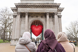 """© Licensed to London News Pictures. 14/02/2018. LONDON, UK. Tourists view a giant chubby heart balloon at Wellington Arc, part of """"Chubby Hearts Over London"""", a design project conceived by Anya Hindmarch.  Supported by the Mayor of London, the British Fashion Council and the City of Westminster giant chubby heart balloons will be suspended over (and sometimes squashed within) London landmarks as a declaration of love to the city starting on Valentine's Day and continuing throughout London Fashion Week.   Photo credit: Stephen Chung/LNP"""