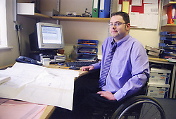 Man with disability; who is wheelchair user; working at desk in office,
