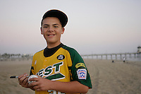 26 September 2011: 2011 Little League Baseball World Series Championship team portrait northside of the Huntington Beach Pier at sunset in Southern California.  Ocean View team WEST beat Hamamtsu City, Japan, 2-1, to become the seventh team from California to win the title on August 28, 2011 in South Williamsport, PA. Pitcher #25 Nick Pratto signs a baseball full of autographs of his teammates while standing on the beach.