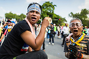 01 DECEMBER 2013 - BANGKOK, THAILAND: Anti-government protestors taunt police before a riot broke out in Bangkok. Thousands of anti-government Thais confronted riot police at Phanitchayakan Intersection, where Rama V and Phitsanoluk Roads intersect, next to Government House (the office of the Prime Minister). Protestors threw rocks, cherry bombs, small explosives and Molotov cocktails at police who responded with waves of tear gas and chemical dispersal weapons. At least four people were killed at a university in suburban Bangkok when gangs of pro-government and anti-government demonstrators clashed. This is the most serious political violence in Thailand since 2010.    PHOTO BY JACK KURTZ