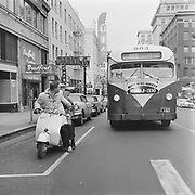 Y-580122-01. Vespa Moto-scout plus city bus on SW Broadway at Taylor. January 22, 1958