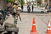 20 MAY 2010 - BANGKOK, THAILAND: Thai soldiers let a motorcycle through a checkpoint at Witthayu Road  in Bangkok Thursday. The day after a military crackdown killed at least six people, Thai authorities continued mopping up operations around the site of the Red Shirt rally stage and battle fires set by Red Shirt supporters in the luxury malls around the intersection. PHOTO BY JACK KURTZ