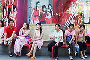 Workers sit in the shade at lunchtime in front of Coca Cola advertising in Shanghai's popular Xiang Yang Fashion Market. It is possible to see from their older style clothes that they are either poor Shanghainese, or migrants from outside Shanghai. The advertising and these people shows the stark contrasts between old China and western modern China, and the gap between rich and poor.