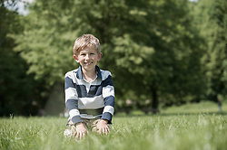 Boy smiling and sitting on a field in park, Munich, Bavaria, Germany