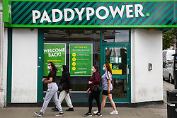 © Licensed to London News Pictures. 14/06/2020. London, UK. Women wearing face coverings walk past a branch of PaddyPower in north London which will reopen on 15 June as coronavirus lockdown restrictions are eased. The government has announced that all betting shops can re-open on Monday 15 June. Betting shops were closed late March following outbreak of COVID-19. Photo credit: Dinendra Haria/LNP