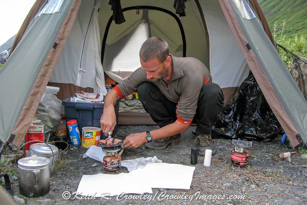 Guide cooking a meal of Dall sheep steaks on a makeshift griddle in the Chugach Mountains of Alaska