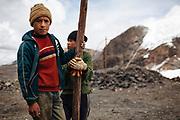 Dos niños toman un descanso del trabajo que realizan en la mina de Rinconada.