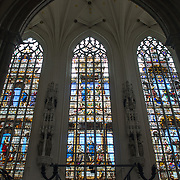 Three narrow stained glass windows at the Cathedral of St. Michael and St. Gudula (in French, Co-Cathédrale collégiale des Ss-Michel et Gudule). A church was founded on this site in the 11th century but the current building dates to the 13th to 15th centuries. The Roman Catholic cathedral is the venue for many state functions such as coronations, royal weddings, and state funerals. It has two patron saints, St Michael and St Gudula, both of whom are also the patron saints of Brussels.