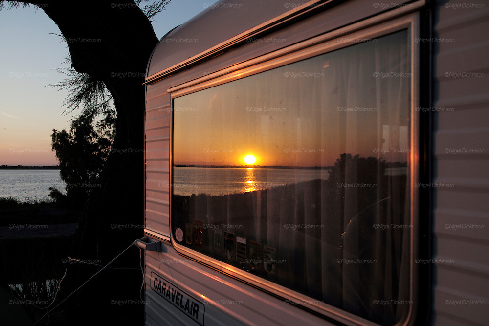 """Manouche camping site, at sunset, on the outskirts of Saintes Maries de la Mer<br /><br />""""Le Pelerinage des Gitans""""; the French gypsy pilgrimage of Saintes Maries de la Mer, Camargue, France<br /><br />Sainte Sara is an uncannonized saint, who legend says looked after the Christian Saints Marie Jacobe and Marie Salome, cousins of Mary Magdalene, who arrived, it is said, on the shores of the Camargue in a rudderless boat. Saint Sara is the patron saint of gypsies who come from far and wide to see her. There are even paintings of Sara as 'Kali' the black saint in Eastern Europe. Sara may have been the priestess of 'Ra' the sun-god or even servant girl to the Christian saints. No-one really knows.<br /><br />For a few weeks of the year, Roma, Gitan and Manouche gypsies come from all over Europe in May, camping in caravans around Saintes Maries de la Mer. It is a festive time where they play music, dance, party and christen their children. They all go to see Saint Sara in the crypt, kissing or touching her forehead. Many put robes on her shoulders, making her fat for the procession. In the main Gypsy procession of the 24th May, Saint Sara is allowed to leave her crypt, beneath the church, and is carried from the church to the shores of the mediterranean and back again. One day a year she is free from her prison. Hundred's of years ago the Gypsies used not even to be allowed into the church, only into the crypt like Sara...<br /><br />Roma gypsies still suffer oppressive prejudice and racism and are one of the ethnic groups the most persecuted and marginalised across Europe. The festival is one of the times where they celebrate with people of all races, their faith and traditions"""