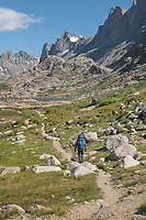 Adult male backpacker with blue backpack and red shirt on Titcomb Basin Trail, Bridger Wilderness, Wind River Range Wyoming