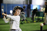 Chester, New York  - A young baseball player takes a swing in the batting cage during the first anniversary open house celebration at The Rock Sports Park on Nov. 12, 2011.