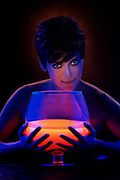Young woman with hands surrounding a large glowing drink.Black light