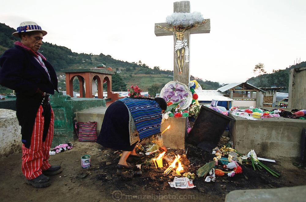 Lighting candles in a graveyard on the Day of the Dead in Todos Santo de Cuchumatan, Guatemala.