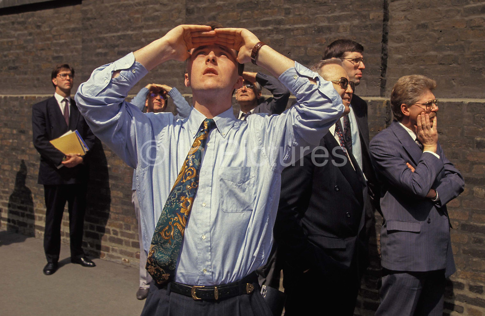City workers look at the damage to buildings caused by the IRA Bishopsgate bomb in the City of London, on 26th April 1993, in London, England. Two days after the Irish Republican Army IRA exploded a truck bomb on Bishopsgate, a main arterial road that travels north-south through Londons financial area, City of London three on-lookers stop to view damage to the tall HSBC building. It was said that Roman remains could be viewed at the bottom of the pit the bomb created. One person was killed when the one ton fertiliser bomb detonated directly outside the medieval St Ethelburgas church. Buildings up to 500 metres away were damaged, with one and a half million square feet 140,000 m of office space being affected and over 500 tonnes of glass broken. repair costs reached approx £350 million.