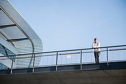 Low angle view of a businessman talking on mobile phone on bridge, Munich, Bavaria, Germany