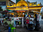"""13 FEBRUARY 2019 - SIHANOUKVILLE, CAMBODIA:  Cambodian street food carts across the street from the Royal Casino, a Chinese casino in Sihanoukville. There are about 80 Chinese casinos and resort hotels open in Sihanoukville and dozens more under construction. The casinos are changing the city, once a sleepy port on Southeast Asia's """"backpacker trail"""" into a booming city. The change is coming with a cost though. Many Cambodian residents of Sihanoukville  have lost their homes to make way for the casinos and the jobs are going to Chinese workers, brought in to build casinos and work in the casinos.      PHOTO BY JACK KURTZ"""