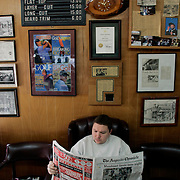 A man reads the newspaper in a local barber shop in Augusta, Georgia.
