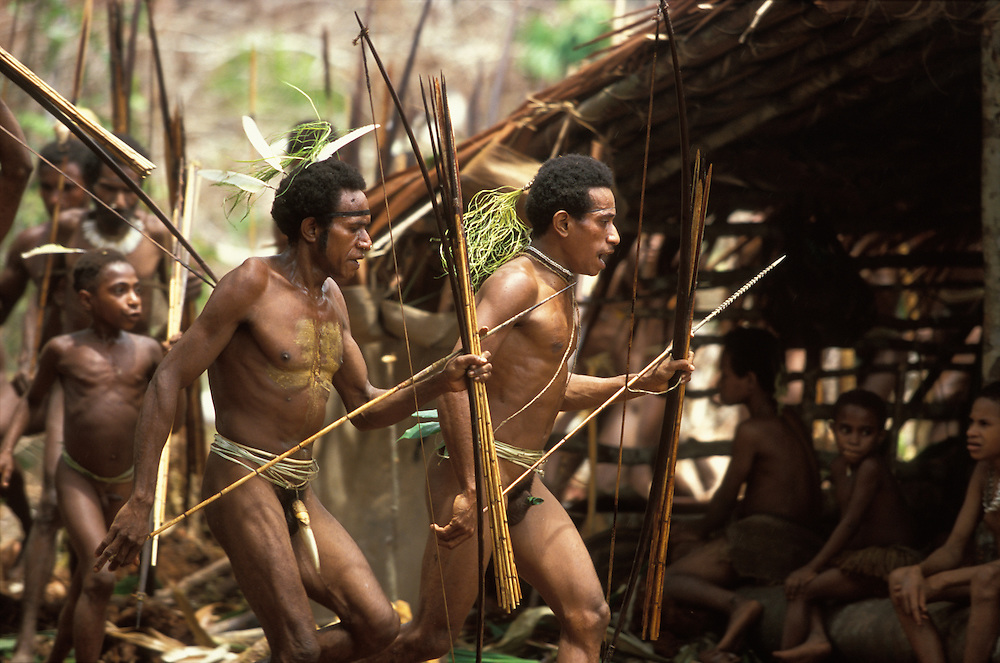 Kombai men, armed with bows and arrows, dance during a sago grub festival in Papua, Indonesia. September 2000. The Kombai are a so-called treehouse people, building their homes high up in the trees, and the sago grub festival, during which large quantities of sago grubs are consumed, is their most important religious rite.