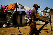 A man passing by drying clothe, carrying a machete. Roça Sundy, Príncipe island