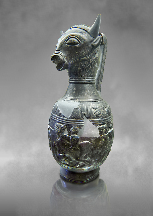 Three quarters view of the 6th century BC Etruscan Bull headed bucherro style oinochoe, or wine jug,  made in Chuisi and excavated from the necropolis de Fonte Rotella, inv 3190, National Archaeological Museum Florence, Italy  , grey art background .<br /> <br /> If you prefer to buy from our ALAMY PHOTO LIBRARY  Collection visit : https://www.alamy.com/portfolio/paul-williams-funkystock - Scroll down and type - Etruscan Florence - into LOWER search box. (TIP - Refine search by adding a background colour as well).<br /> <br /> Visit our ETRUSCAN PHOTO COLLECTIONS for more photos to download or buy as wall art prints https://funkystock.photoshelter.com/gallery-collection/Pictures-Images-of-Etruscan-Historic-Sites-Art-Artefacts-Antiquities/C0000GgxRXWVMLyc