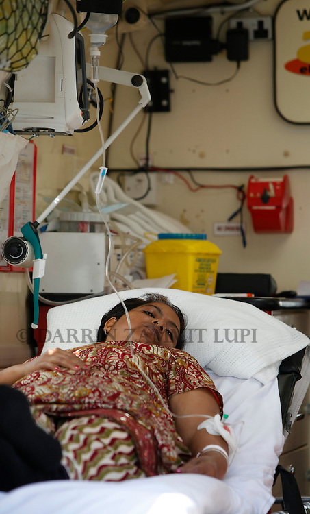 An Indian woman in need of medical attention lies in an ambulance after disembarking from the ferry MV Red Star One after arriving at Valletta's Grand Harbour March 6, 2011.  The Indian-chartered ferry arrived in Malta from Misurata in Libya on Sunday morning carrying 301 passengers, mostly Indians but also including Filipino, British and Bangladeshi nationals...REUTERS/Darrin Zammit Lupi (MALTA)