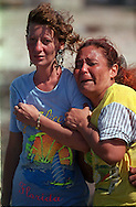 8/1994-Al Diaz/Miami Herald--Idelisa Gonzalez, right, cries and prays to God as her only daughter leaves the tiny fishing village of Cojimar, Cuba on a makeshift raft. The woman at left is unidentified. For the loved ones left behind. there was the anguish of not knowing whether they'd see their husband, wives, sons or daughters ever again. It was mostly women who stayed. More than 80 percent of the rafters were male.