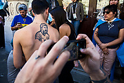 Moscow, Russia, 15/06/2018.<br /> A passer-by photographs an Argentine supporter with a Lionel Messi tattoo on his back in central Moscow during the 2018 FIFA World Cup.