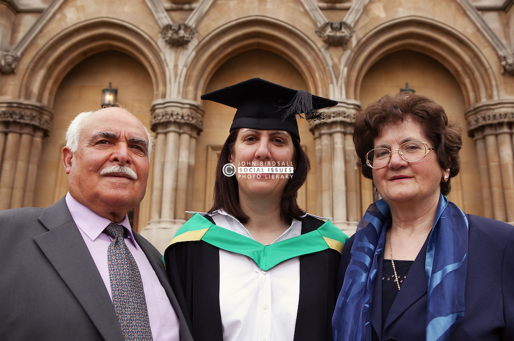 Portrait of woman in graduation gown with her parents,