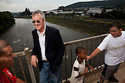 """BETHLEHEM, PA – JUNE 17, 2011: Attorney Fred Rooney lets a group of Hispanic children pass by on the Fahy bridge in Bethlehem, Pennsylvania. Rooney is the founding director of CUNY Law School's Community Legal Resource Network in New York, a virtual law firm that seeks to increase access to justice for people who cannot afford legal help. As Bethlehem native, Rooney attributes the success of the firm to his deep roots in the Hispanic culture of the Lehigh Valley. """"I've been living and breathing it for the greatest part of my life,"""" he said. """"I feel very grateful, blessed and fortunate for the things I've learned from the community."""" The Fahy bridge connects the historically Hispanic south side of Bethlehem to the predominantly white north."""