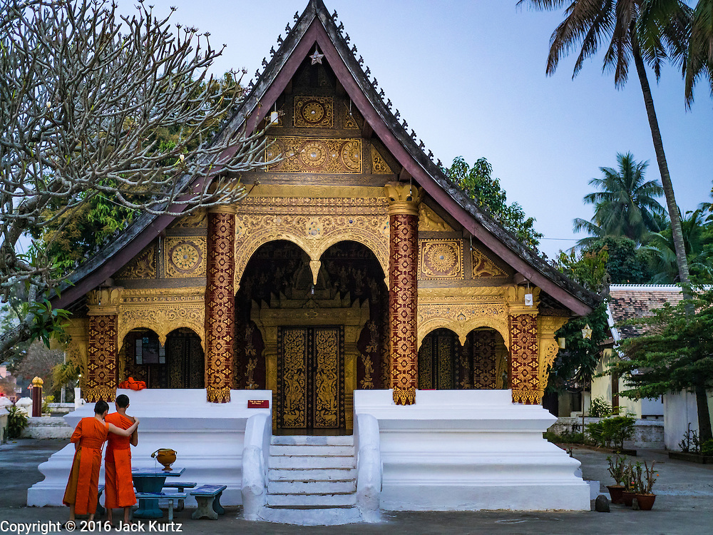 """11 MARCH 2016 - LUANG PRABANG, LAOS:  Buddhist monks wait to start the morning tak bat in Luang Prabang. Luang Prabang was named a UNESCO World Heritage Site in 1995. The move saved the city's colonial architecture but the explosion of mass tourism has taken a toll on the city's soul. According to one recent study, a small plot of land that sold for $8,000 three years ago now goes for $120,000. Many longtime residents are selling their homes and moving to small developments around the city. The old homes are then converted to guesthouses, restaurants and spas. The city is famous for the morning """"tak bat,"""" or monks' morning alms rounds. Every morning hundreds of Buddhist monks come out before dawn and walk in a silent procession through the city accepting alms from residents. Now, most of the people presenting alms to the monks are tourists, since so many Lao people have moved outside of the city center. About 50,000 people are thought to live in the Luang Prabang area, the city received more than 530,000 tourists in 2014.      PHOTO BY JACK KURTZ"""