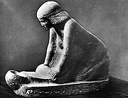 Egyptian woman grinding corn using a saddle quern. Egyptian tomb figure c 2,500 BC. Photograph c1910.