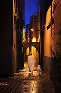 Man with his daughter walking through the old streets in the Medina, Essaouira, Morocco