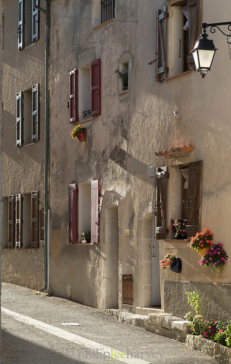 Facade of old tenement house with open windows and shutters, Village of Rougon, France