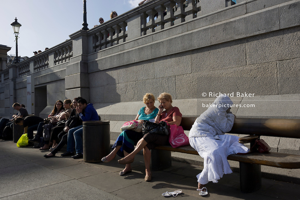 A lonely-looking woman appears isolated in the company of tourists and visitors to London's Trafalgar Square.
