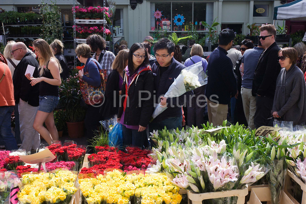 As crowds walk past fresh roses and lilies in Columbia Road flower market, in north London, a young Asian couple browse other blooms on show. Beautiful lilies still to flower are in cellophane and yellow roses have produced stunning colour to lure city gardeners and homeowners to this well-known market on a Saturday morning. Sellers shout out their current bargains and shops sell everything from hats and couture to antiques and cakes.