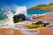 Crashing surf at Secret Beach (Kauapea Beach), Kilauea Lighthouse visible, Kauai, Hawaii USA