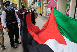 London, UK. 11th May, 2021. A Metropolitan Police officer asks activists from Palestine Action to move back during a protest outside the UK headquarters of Elbit Systems, an Israel-based company developing technologies used for military applications including drones, precision guidance, surveillance and intruder-detection systems. The activists were protesting against the company's presence in the UK and in solidarity with the Palestinian people following attempts at forced evictions of Palestinian families in the Sheikh Jarrah neighbourhood of East Jerusalem, the deployment of Israeli forces against worshippers at the Al-Aqsa mosque during Ramadan and air strikes on Gaza which have killed several children.