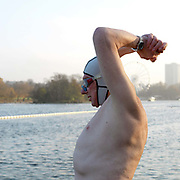 Jeremy Hunter, a member of the Serpentine Swimming Club, stretches before swimming in the Serpentine Lake, Hyde Park, London, UK. The Serpentine Lake is situated in Hyde Park, London's largest central open space. The Serpentine Swimming Club was formed in 1864 'to promote the healthful habit of bathing in open water throughout the year'.  Its headquarters were beneath an old elm tree on the south side of the lake, a wooden bench for clothing being the only facility.  At this time London was undergoing rapid expansion and Hyde Park was now in the centre of a densely populated built up area and provided a place of relaxation to its urbanised masses. Now, the club has its own (somewhat spartan) changing facilities and members are  permitted by the Royal Parks to swim in the lake any morning before 09:30.  They race every Saturday morning throughout the year, regardless of the weather.