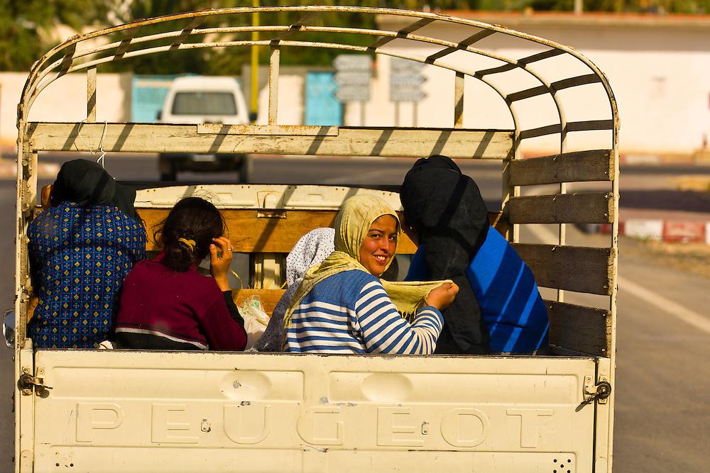 Women riding in the back of a truck in Tatouine, Tunisia