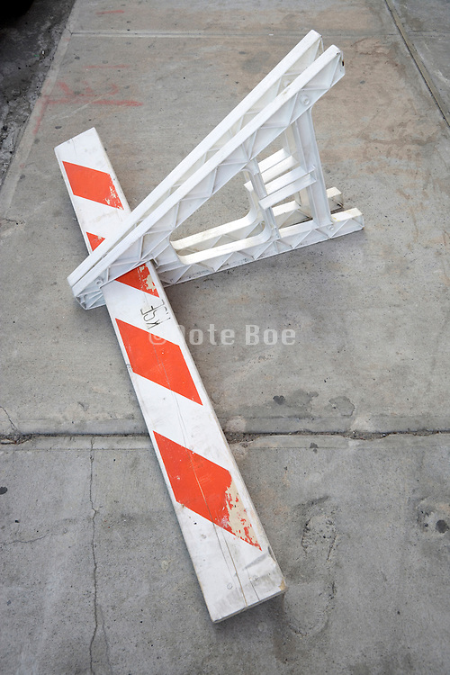 fallen over sawhorse on the side of the road