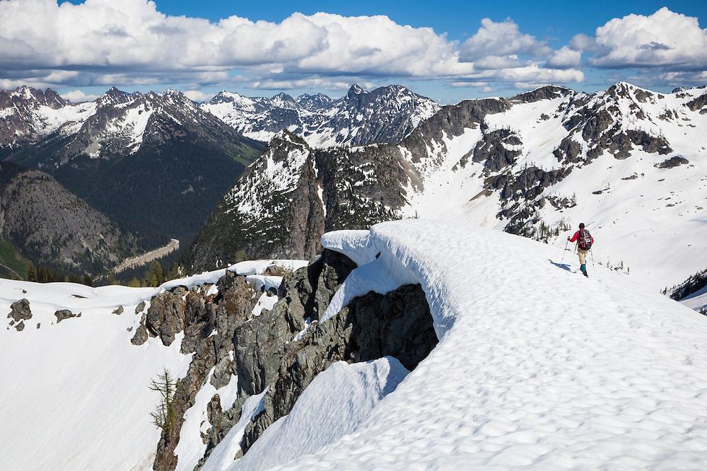 Parmenter Welty hikes a corniced ridge between Ann and Rainy Lakes, North Cascades Scenic Highway Corridor, Washington.