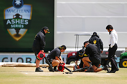 Groundstaff attempt to dry the pitch during day five of the Ashes Test match at the WACA Ground, Perth.