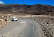 Car unsurfaced road, barren rocky mountains, Jandia peninsula, Fuerteventura, Canary Islands, Spain