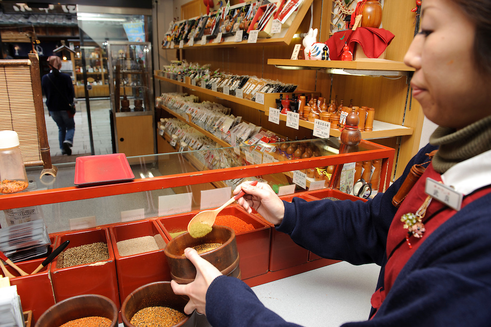 Shop assistant holds a bowl of freshly mixed shichimi, Yagenbori shichimi, Asakusa, Tokyo, Japan, February 19, 2011.Yagenbori, founded in 1625 was the first to produce the now popular Japanese condiment.