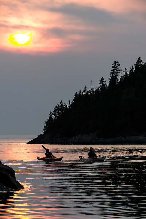 """Two kayakers in silhouette paddle their kayaks at sunset on Baie de l'Isle-Verte (French for """"Green Island Bay"""") along the southern shore of the Saint Lawrence River in Quebec, Canada."""