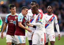 Burnley's Ashley Westwood and Crystal Palace's Wilfried Zaha (right) are kept apart by their team-mates during the Premier League match at Turf Moor, Burnley.