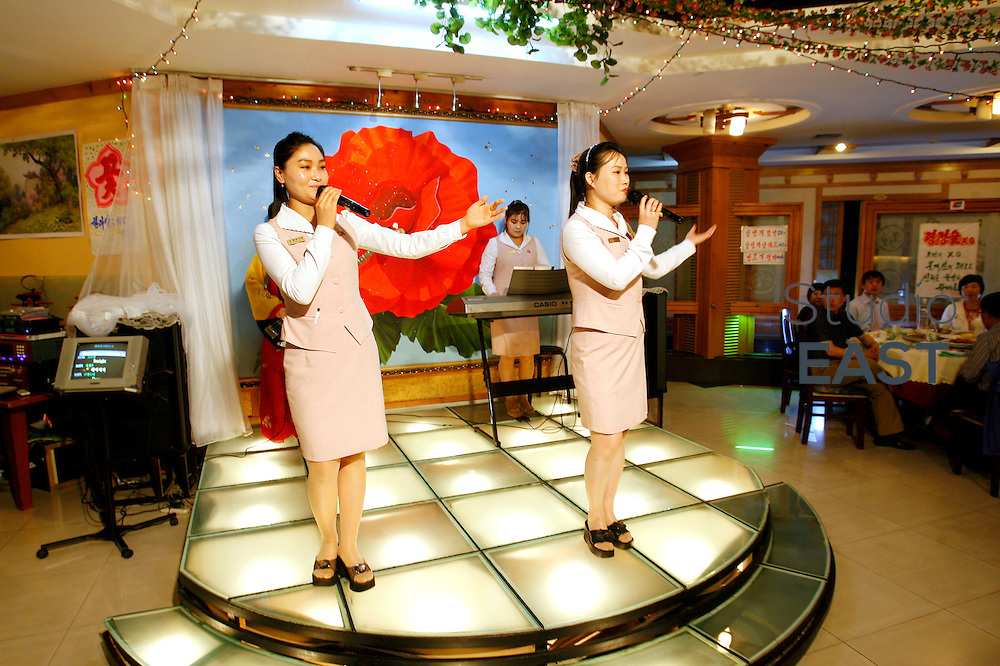 JILIN PROVINCE, CHINA - May 08: North Korean waitresses sing and entertain the audience at a North Korean restaurant on May 8, 2009 in Tonghua, Jilin province, China. This restaurant is unique: it is the only North Korean restaurant with North Korean staff in China. The ten North Korean waitresses here are ones of the very few North Koreans, others than diplomats, allowed out of their country. All of them able to sing and dance, they come to China for 3-years internship, missing very much their family left in North Korea. (Photo by Lucas Schifres/Getty Images)