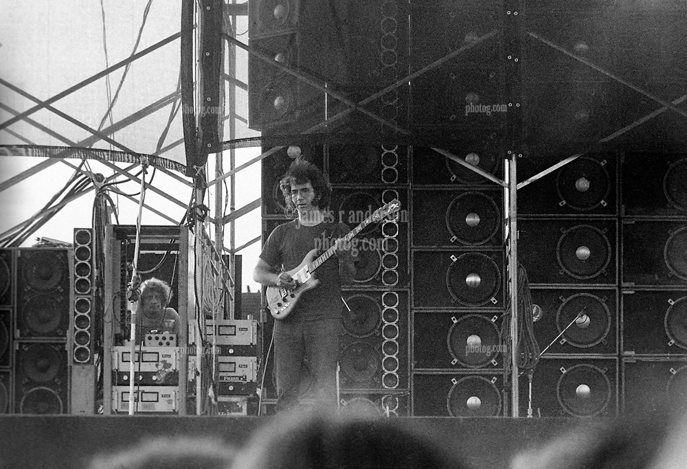 Jerry Garcia performing with The Grateful Dead. In Concert at Dillon Stadium on 31 July 1974. During the first set or beginning of the second set. This is close to full frame of the film showing more speakers. Photograph shot with a Nikon FTn Camera and Kodak Tri-X B&W Film.